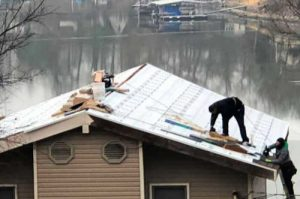 Roofer performing home roof repair services at lake ozark