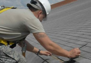 Military worker performing roof repair in Lake Ozark, MO.