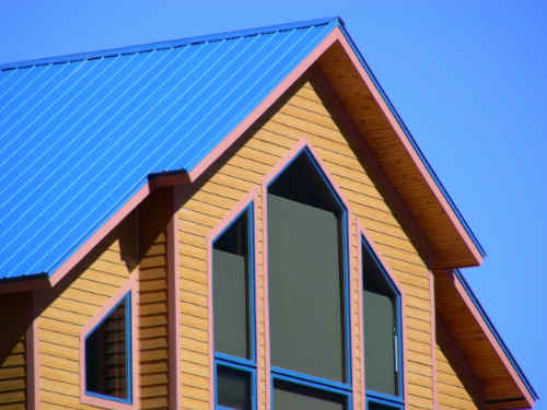 Blue metal roof and large picture windows in a lake home.