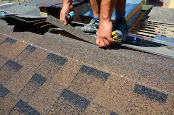 A roofer laying brown asphalt shingles on a roof.