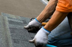 Roofer installing a new asphalt shingle on a roof.