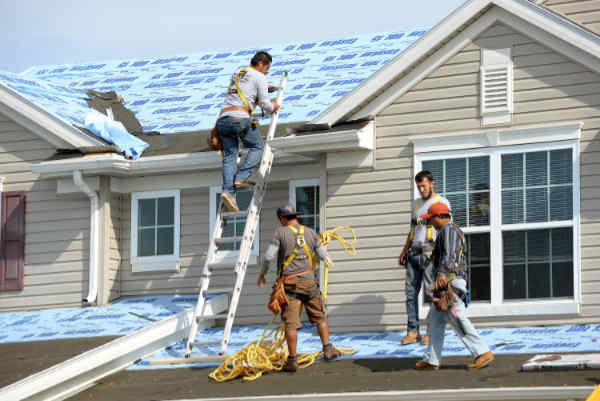Roofing company crew at work on a home roof.