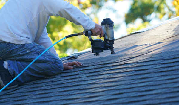Roofer nailing down asphalt shingles with an air nailing gun.