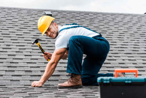 Roofer nailing down shingles on a roof.
