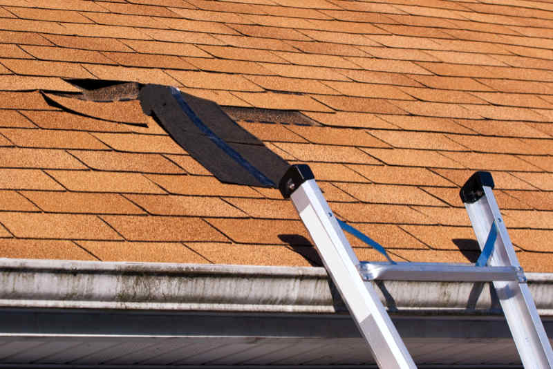 An asphalt shingle is torn loose from roof and just hanging