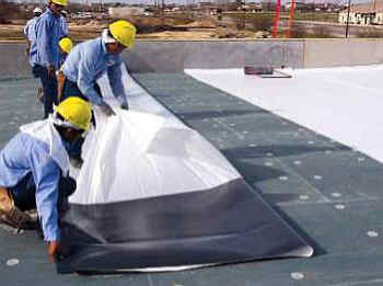 Roofers installing TPO roofing membrane on a flat roof