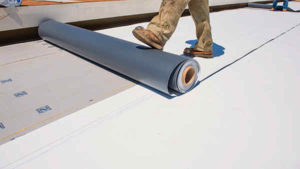 Roofer rolling out TPO roofing membrane during installation