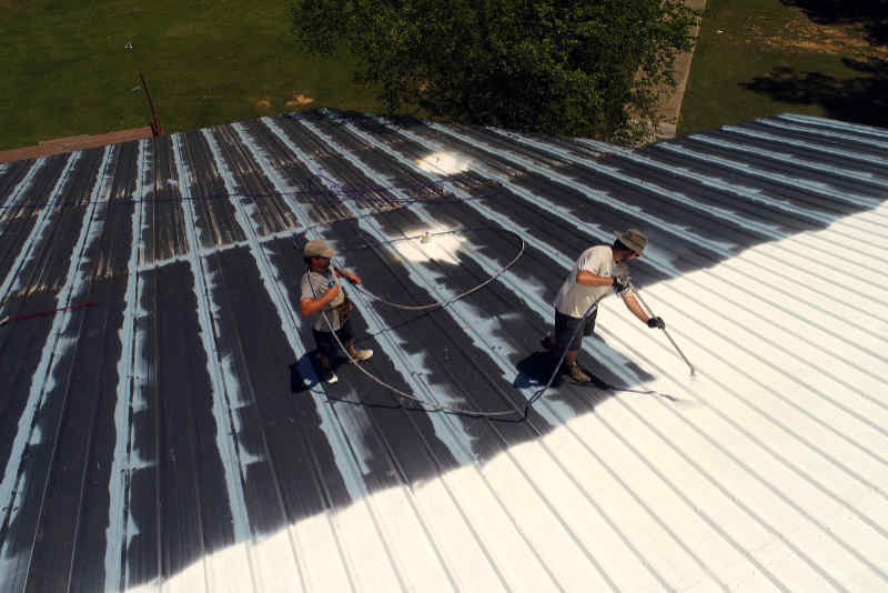 Two roofers spraying a large commercial metal roof with elastomeric coating.