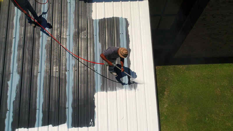 Two men spraying foam roofing on a flat metal roof in Lake Ozark, Missouri.