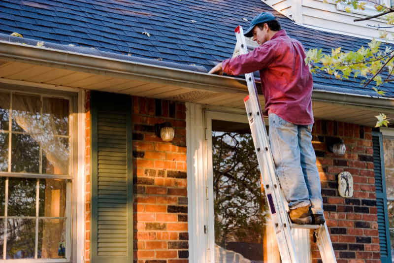 Man Cleaning Gutters on Ladder