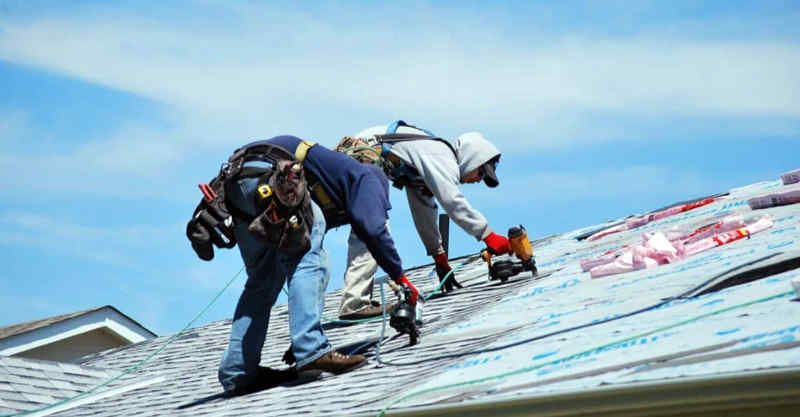Two roofers nailing down asphalt shingles