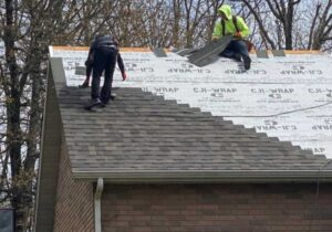 Two roofers installing architectural shingles on a brick home in the fall