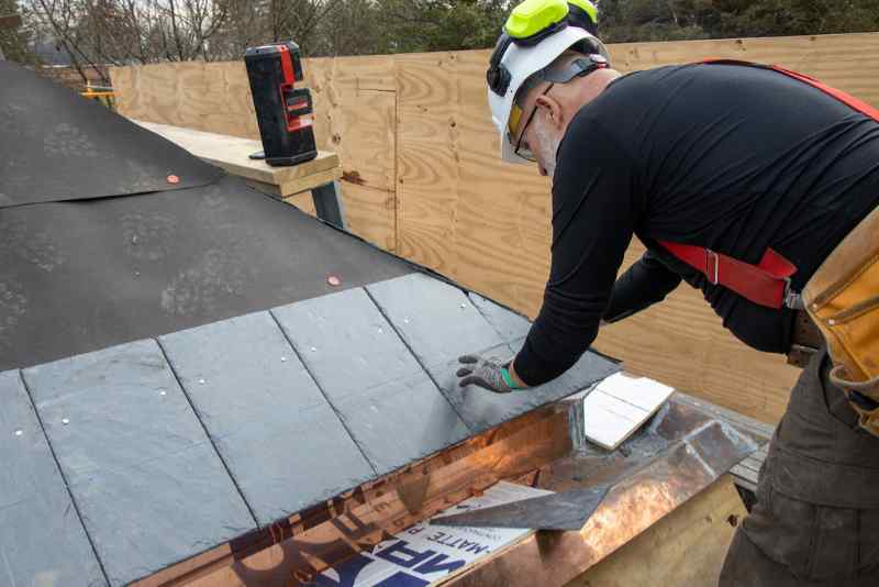 Man snapping a chalk line while installing a natural slate roof tiles