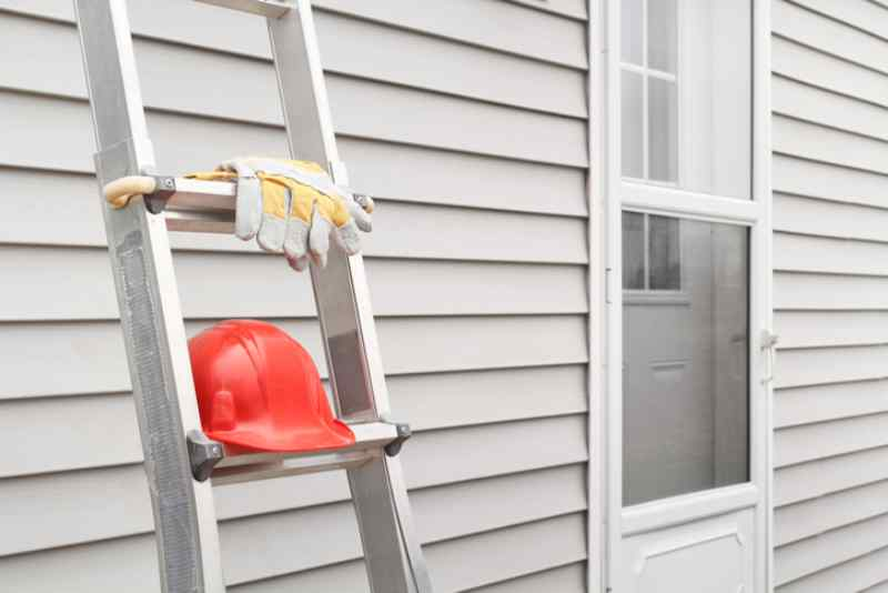 Red hard hat and work gloves on a ladder with house siding background.