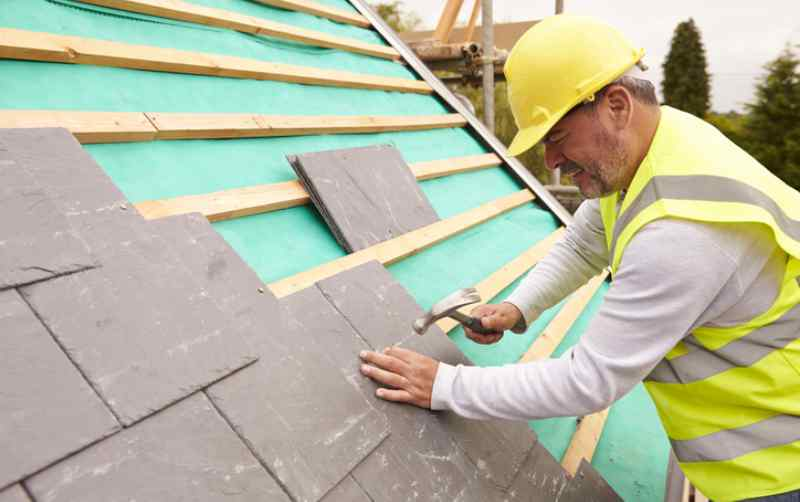 Construction worker on building site installing slate tiles