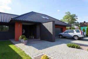 A home with a garage and paved parking and an interesting modern roof and house color combination