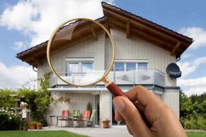 Person's Hand Holding Magnifying Glass Over Luxury House