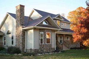 Beige and stone lake house with standing seam metal roofing in the Fall