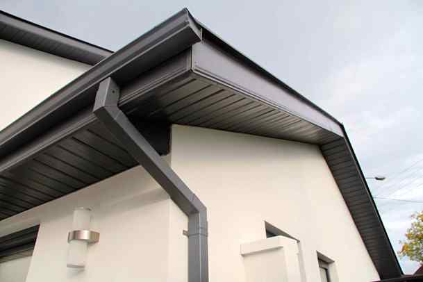 New black aluminum fascia trims the roof on a white house