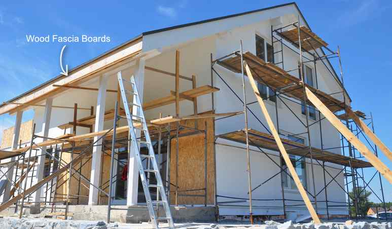 Modern house repair and renovation. Plastering, applying stucco and painting the wood fascia board and walls during the renovation.